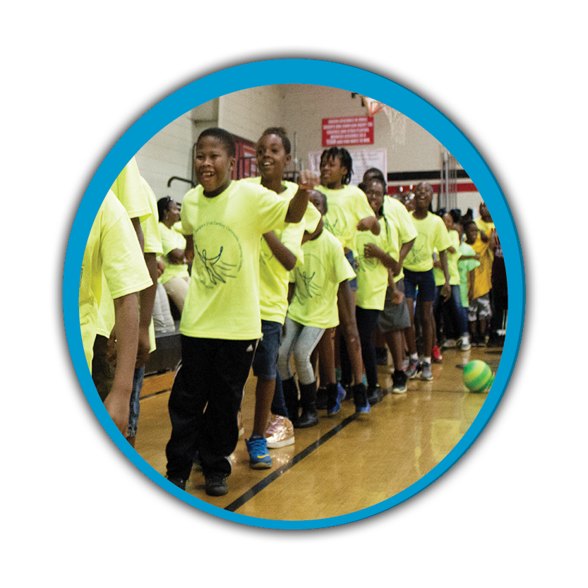 A dozen students wearing bright yellow shirts lined up in a gym