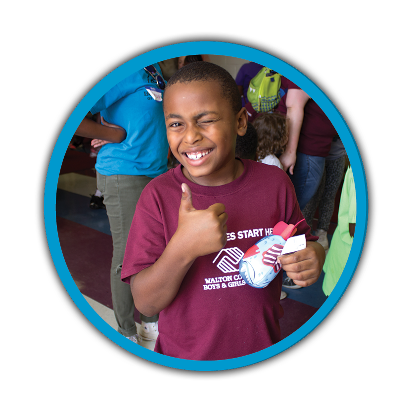 A young student wearing a maroon shirt smiling with a thumbs up